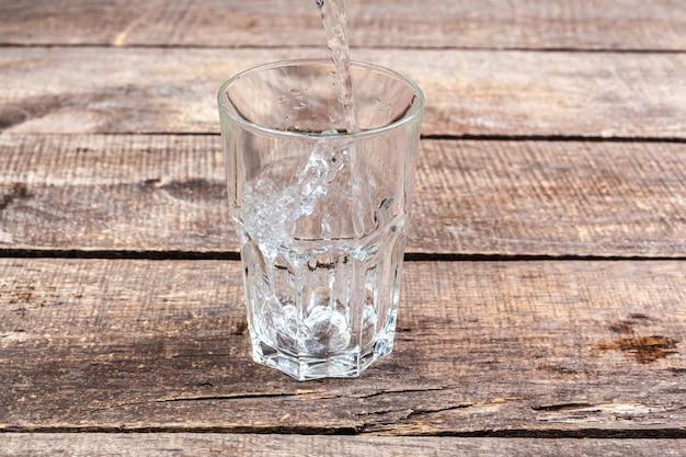 Vasos de agua sobre una mesa de madera. Foto Premium