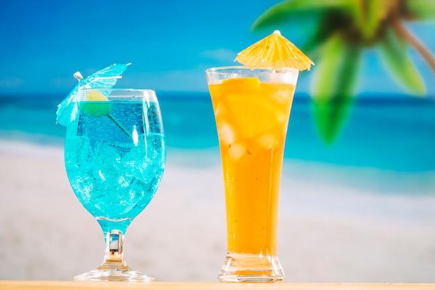 Vasos de bebida fresca azul naranja decorada con oliva y paraguas Foto gratis