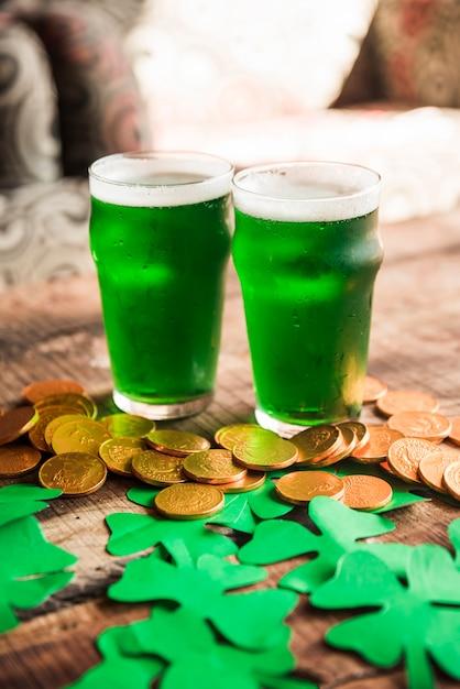 Vasos de bebida verde cerca de montón de monedas y tréboles de papel Foto gratis