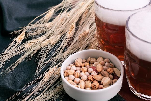 Vasos de cerveza con surtido de aperitivos en un tazón Foto gratis