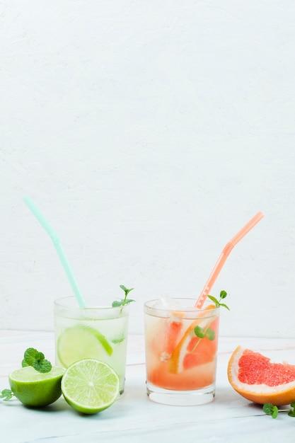 Vasos de fruta fría con pajitas Foto gratis