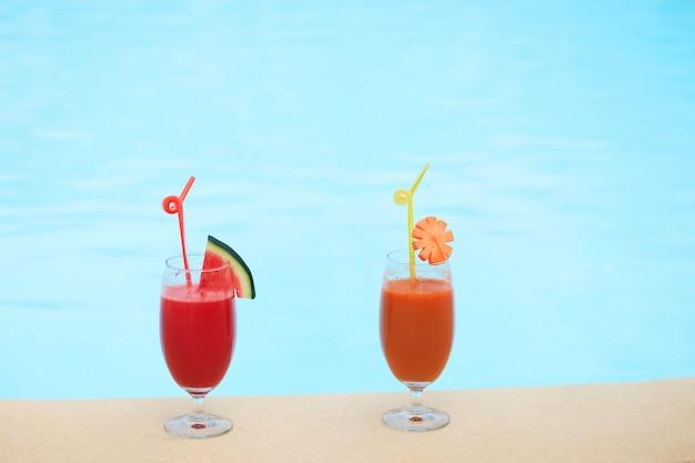 Vasos de jugo fresco sentado en el borde de la piscina Foto gratis