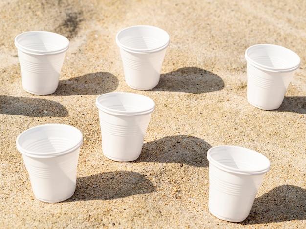 Vasos de plástico en la arena de la playa Foto gratis
