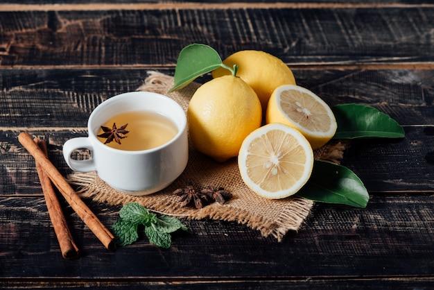 Vasos de té con limón, limones en rodajas sobre una tabla de cortar Foto gratis