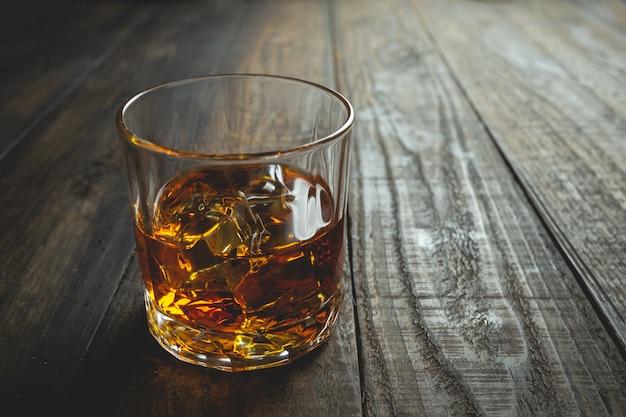 Vasos de whisky con cubitos de hielo sobre madera. Foto gratis
