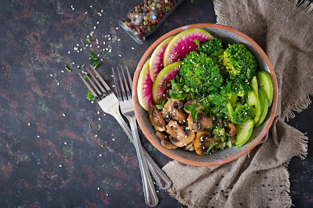 Vegano buda tazón cena mesa de comida. comida sana. tazón de almuerzo vegano saludable. champiñones a la plancha, brócoli, ensalada de rábano. endecha plana. . Foto Premium