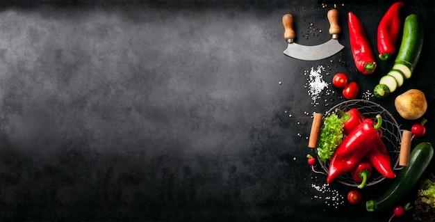 Vegetales y un cuchillo italiano puestos a la izquierda de una mesa negra Foto gratis