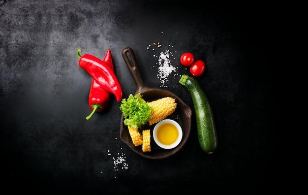 Vegetales y un cuchillo italiano puestos en una mesa negra Foto gratis