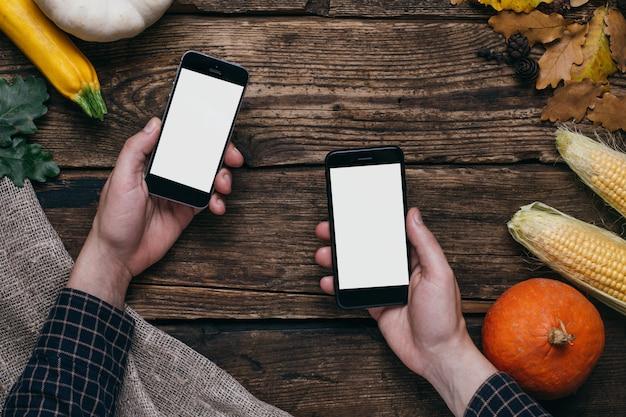 Vegetales de otoño: teléfono móvil con pantalla blanca vacía en la mano del hombre, calabazas y maíz en madera Foto Premium