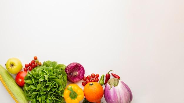 Vegetales saludables llenos de vitaminas sobre fondo blanco con espacio de copia Foto gratis