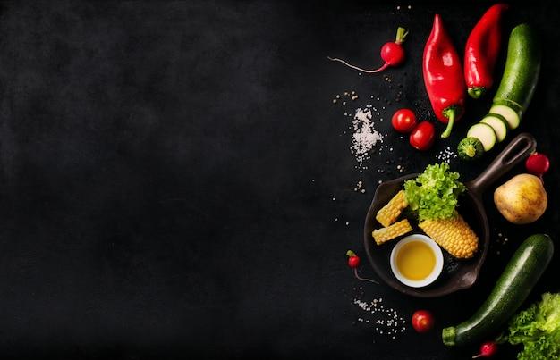 Vegetales varios sobre una mesa negra con espacio para un mensaje Foto gratis