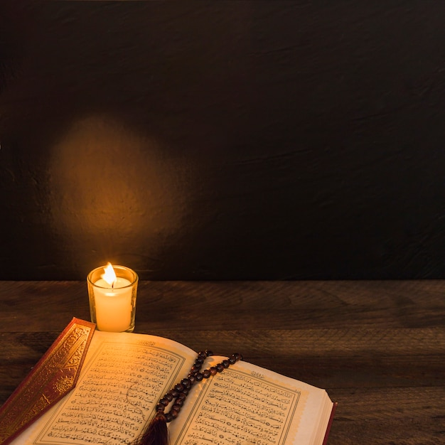Vela y corán con cuentas en cuarto oscuro Foto gratis