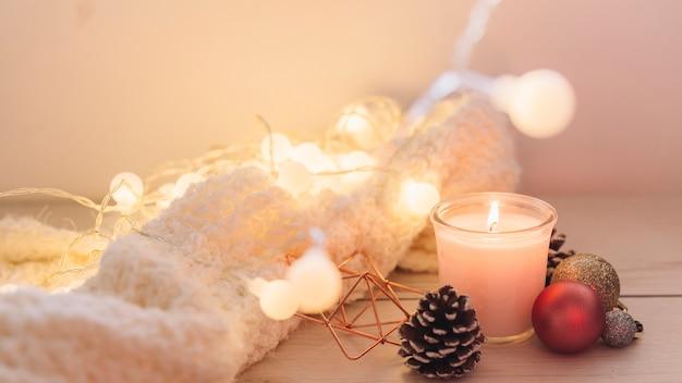 Vela encendida con bufanda en mesa Foto gratis