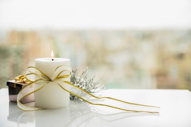 Vela encendida con lazo junto a la ventana Foto gratis