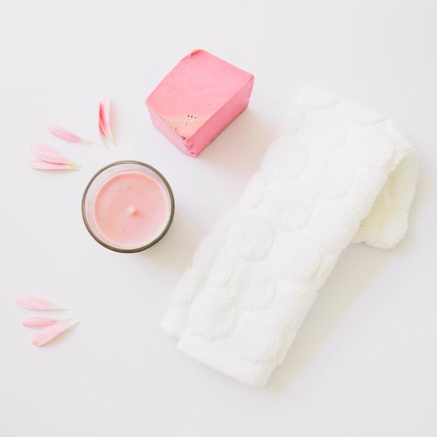 Vela; pétalos de gerbera; barra de jabón y servilleta blanca aislada sobre fondo blanco Foto gratis