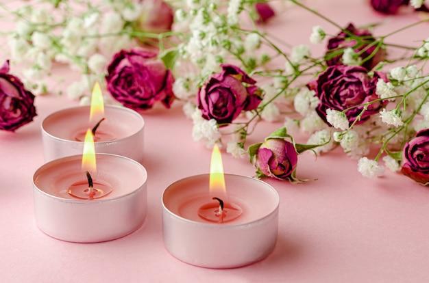 Velas aromáticas encendidas y rosas secas en rosa. concepto de aromaterapia  y romance. | Foto Premium