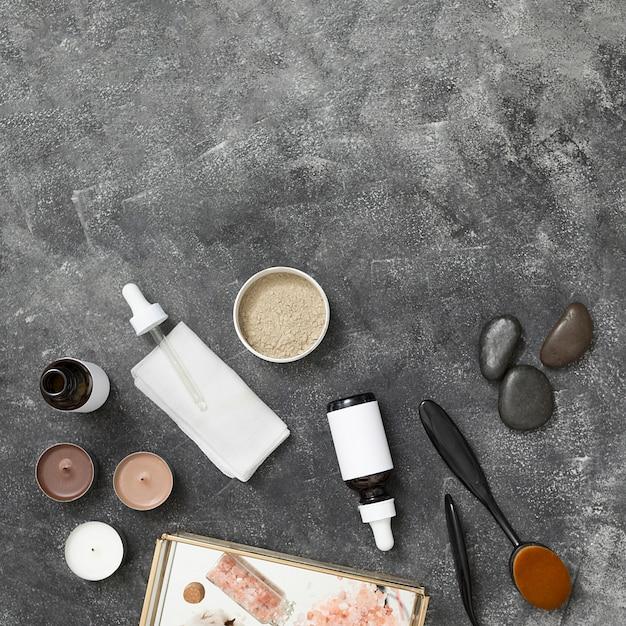 Velas botella de aceite esencial; arcilla rhassoul; el último; sal de roca del himalaya en una bandeja con fondo de hormigón negro Foto gratis