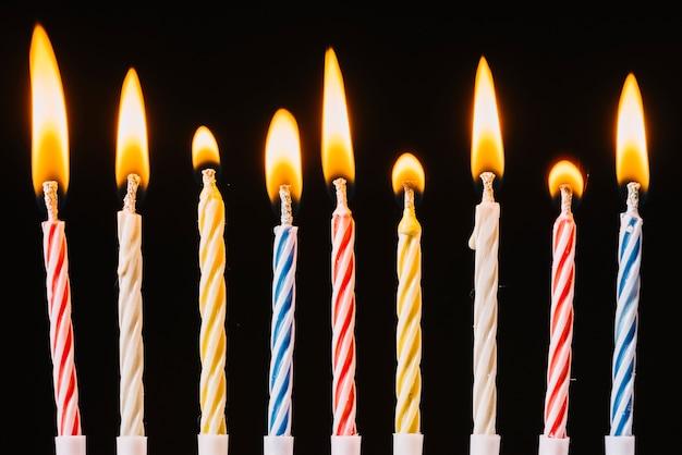 Velas de cumpleaños ardientes sobre fondo negro Foto gratis