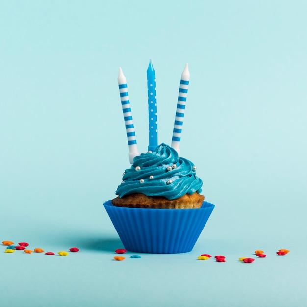 Velas decorativas en muffins con estrella rociada contra Foto gratis