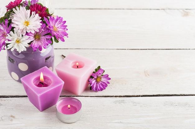 Velas encendidas de color púrpura y flores de jardín rosadas Foto Premium