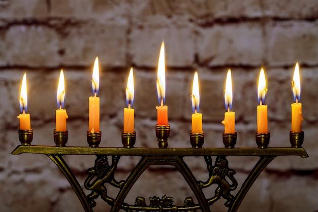 Velas encendidas de januca en una menorá en coloridas velas de una menorá Foto Premium