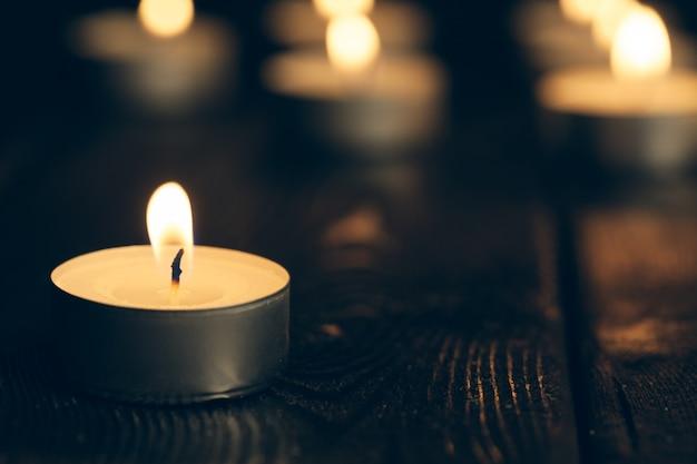 Velas encendidas en la oscuridad sobre negro. concepto de conmemoración Foto Premium