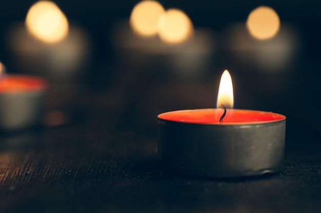 Velas encendidas en la oscuridad sobre negro. conmemoración Foto Premium