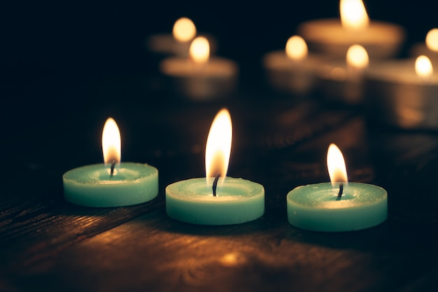 Velas encendidas en la oscuridad sobre negro. Foto Premium