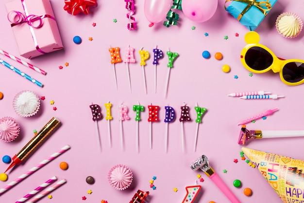 Velas de feliz cumpleaños rodeadas de serpentinas; gemas aalaw; sombrero de fiesta y cuerno de fiesta sobre fondo rosa Foto gratis