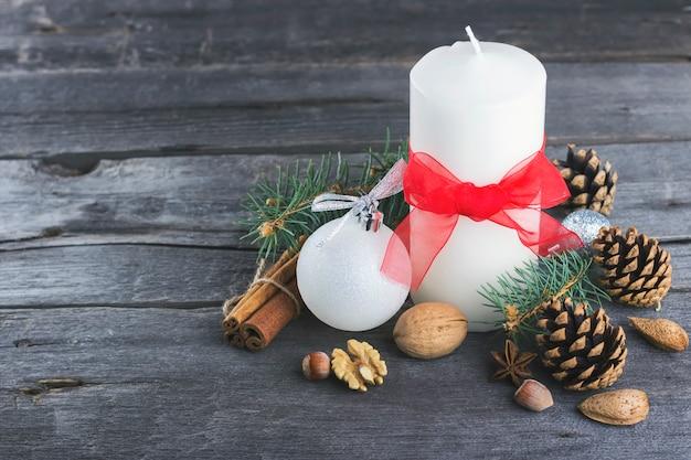 Velas festivas, abeto con árbol, piñas, nueces sobre una superficie de madera Foto Premium