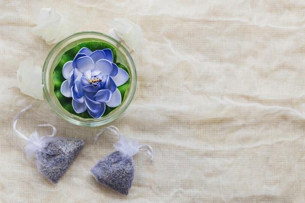 Velas en forma de loto y bolsas con hierbas Foto gratis
