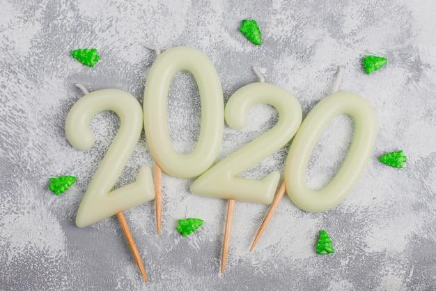 Velas en forma de números 2020 como símbolo del año nuevo junto a dulces con forma de navidad en una mesa gris. vista superior, endecha plana Foto gratis