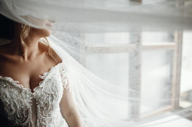 El velo cubre la cara de la novia mientras ella se para ante la ventana. Foto gratis