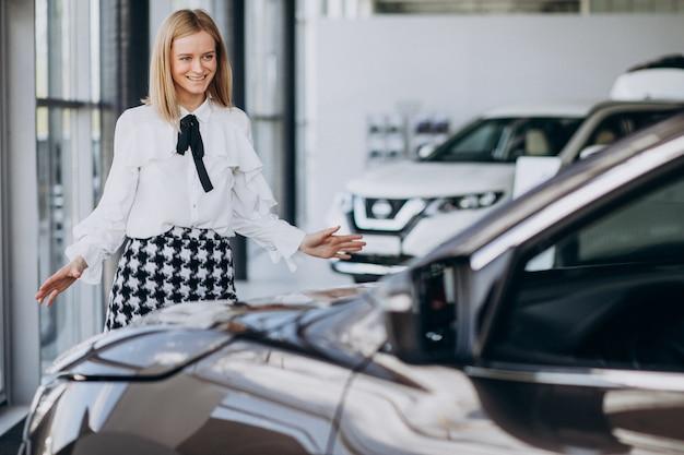Vendedor femenino en una sala de exposición de automóviles de pie junto al coche Foto gratis
