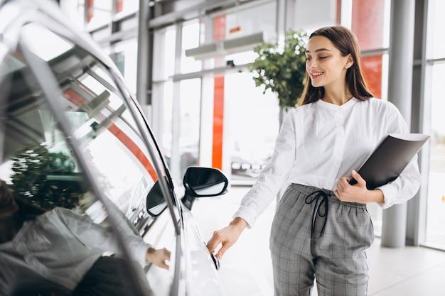 Vendedor femenino en una sala de exposición de automóviles Foto gratis