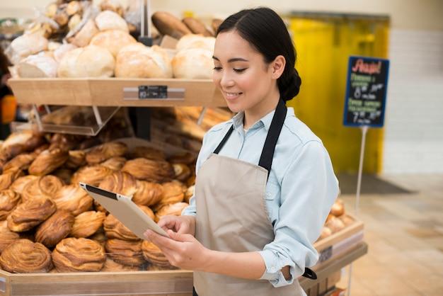 Vendedor de sexo femenino asiático sonriente de la panadería que se coloca con la tableta en supermercado Foto gratis