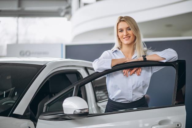 Vendedor de sexo femenino en una sala de exposición del coche Foto gratis