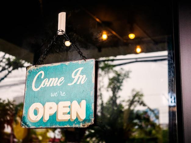 Venga, estamos abiertos, firme en la puerta de la cafetería. Foto Premium