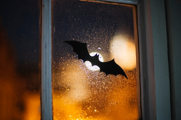 Ventana de decoración de halloween papel bat cubierto con gotas de lluvia Foto gratis