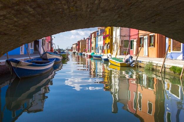 Ver debajo del puente en la típica escena de una calle que muestra casas pintadas de vivos colores y barcos con reflejos a lo largo del canal en las islas de burano en venecia, italia Foto Premium
