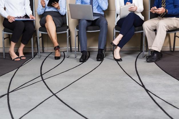 Ver recortada de negocios que se sientan en fila Foto gratis