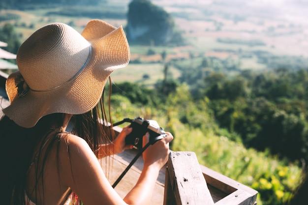 Verano hermosa chica sosteniendo una cámara con vista a la montaña Foto gratis