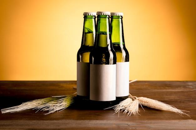 Verdes botellas de alcohol en mesa de madera Foto gratis