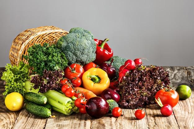Las verduras de una cesta en la mesa de madera Foto gratis