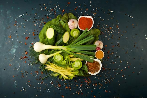 Verduras y especias frescas en una tabla de madera redonda en una piedra oscura. el concepto de vintage. especias el espárrago de maíz joven pepino de tomate verde en una superficie oscura. Foto Premium