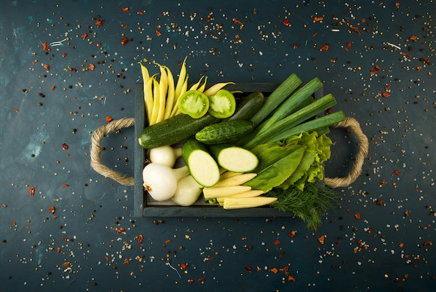 Verduras frescas en caja de madera en una piedra oscura. el concepto de vintage. el espárrago de cebollas jovenes tomate verde pepino en una superficie oscura. Foto Premium