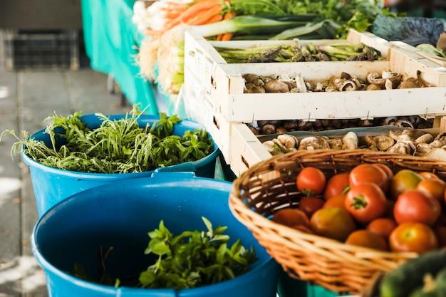 Verduras frescas con setas en cajón de madera en puesto de mercado Foto gratis