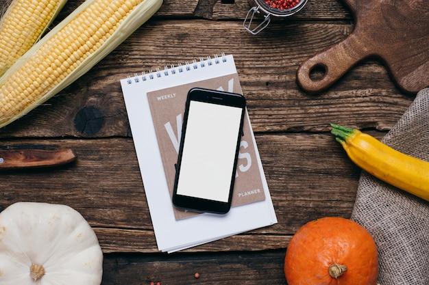 Verduras de otoño: teléfono móvil con pantalla blanca vacía, calabazas y maíz con hojas amarillas en madera Foto Premium