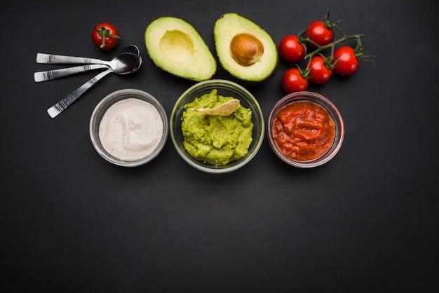 Verduras y salsas en tazones cerca de cucharas Foto Premium