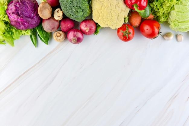 Verduras sanas coloridas frescas en el fondo de mármol de la encimera Foto Premium